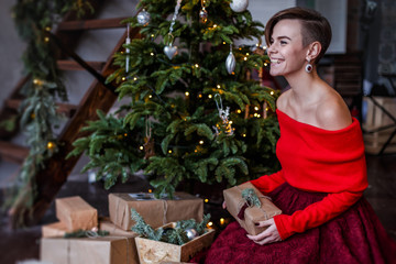 Smiling beautiful woman is posing around the Christmas tree with different boxes full of gifts