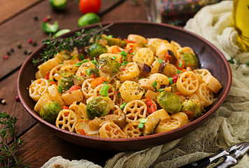 Vegetarian Vegetable pasta Rocchetti with brussels sprouts, tomato, eggplant and paprika in brown bowl on wooden table