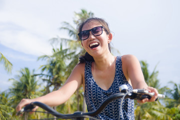 young happy and pretty Asian Chinese woman riding bike in Vietnam or Thailand tropical jungle forest with palm trees smiling relaxed