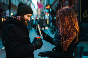 Woman pouring drink to man on street