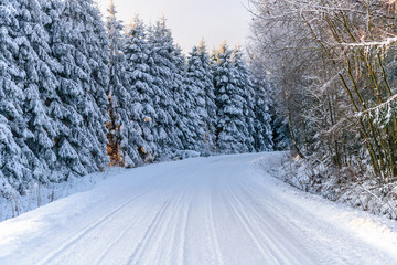 Winter landscape - snow covered mountain road in the forest on a cold and sunny morning