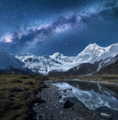 Poster Reflection Milky Way and high mountains. Night landscape with mountains and starry sky reflected in water in Nepal. Lake, rocks with snowy peak and sky with stars. Himalayas. Fantastic scene with milky way