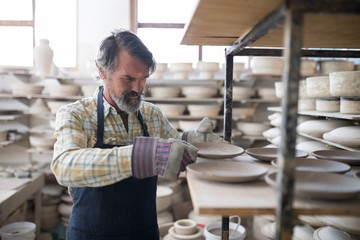 Male potter placing plate on shelf