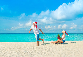 Cheerful couple in red Santa hats walking at tropical ocean sandy beach with sleds, decorated fir-tree and gift boxes. Happy New Year and Merry Christmas vacation concept.