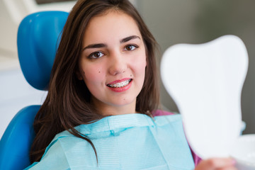 Beautiful girl with braces smiles in dentistry.