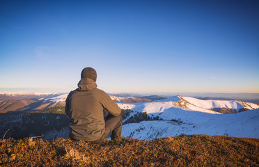 Man sitting on a hill and look to the valley