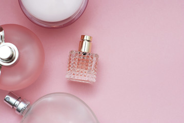Perfume bottles pink background. Perfumery, cosmetics, fragrance collection. Flat lay with Copy Space. Women and Mother Day.