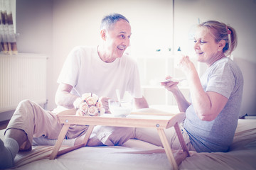 Senior people drinking coffee in bed.