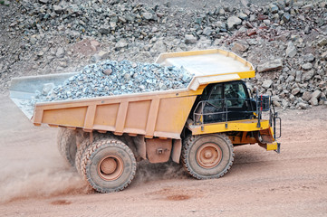 dumper truck driving in an active quarry mine of porphyry rocks. digging.