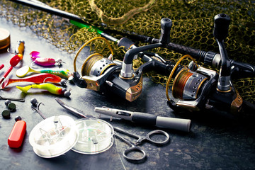 Photo sur Aluminium Peche Fishing rods and spinnings in the composition with accessories for fishing on the old background on the table