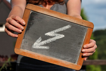 flash sketched with chalk on slate shown by young female