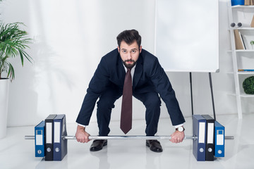 businessman in suit weightlifting folders in office
