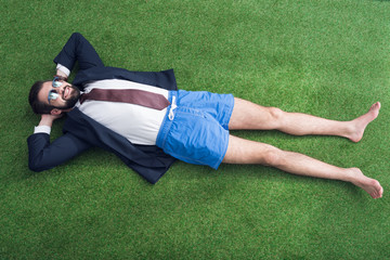 overhead view of businessman in jacket and shorts resting on green lawn