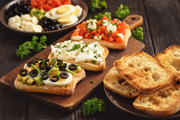 Variety of sandwiches with tomatoes, mozzarella, avocado, eggs and cream cheese.