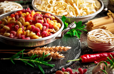 Raw pasta in the composition on the table with items for cooking