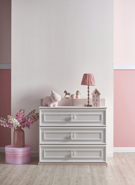 new born girl baby room with white furniture and toys
