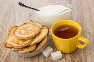 Pancakes in bowl, sour cream, tea and lumpy sugar