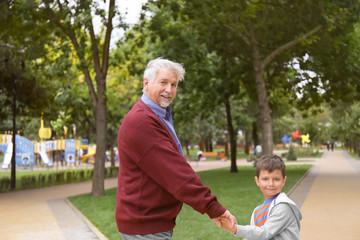Happy senior man with grandson in park