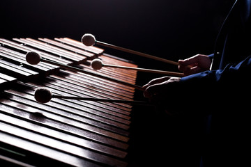 The hands of a musician playing the marimba in dark tones