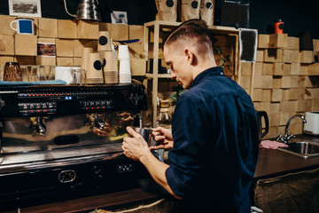 Handsome barista preparing cup of coffee for customer in coffee shop. Retro picture with little noise.