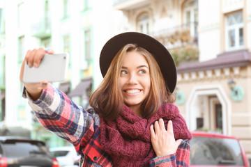 Young beautiful woman taking selfie outdoors