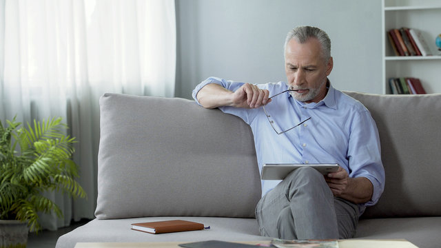 Adult male sitting on sofa and reading news on tablet, modern technologies