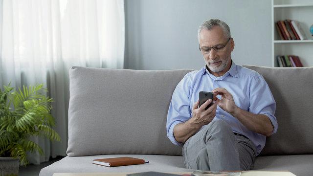 Kind senior man typing telephone number on cellphone, modern technologies