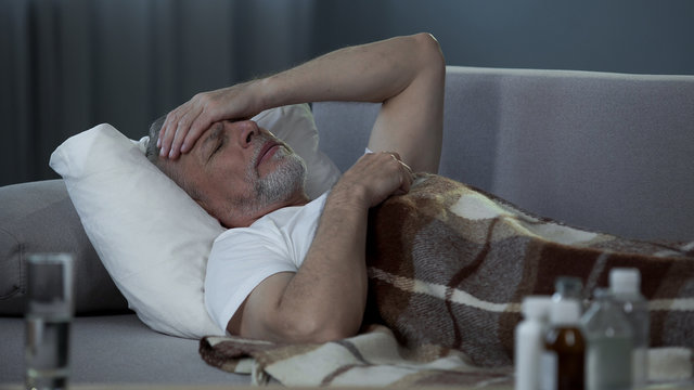 Ill senior male lying in bed and suffering from terrible headache, disease