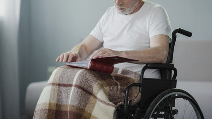 Paralyzed senior male reviewing album with photos, missing his family support