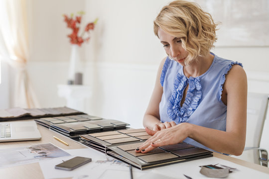 Pretty Caucasian woman interior designer working with material palette at her office.