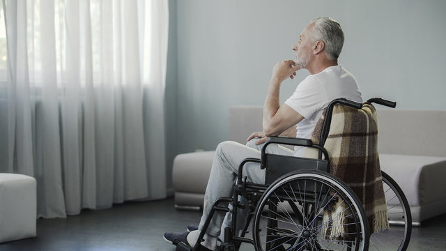 Thoughtful retired male sitting in wheelchair and looking in the window, disease