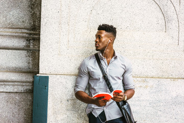 Modern College Student in New York. Wearing gray shirt, wristwatch, carrying shoulder leather bag, an African American guy standing by wall on street, listening music with earphone, reading red book..