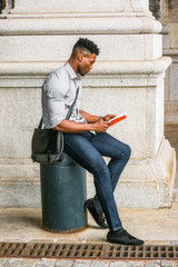 African American College Student studying in New York. Wearing gray shirt, jeans, cloth shoes, carrying shoulder leather bag, a black man sitting on metal pillar on street, relaxing, reading red book