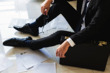 Stressed and sad businessman sitting on floor by scattered working paper files in empty office. Closeup suffer man lay on the ground after getting fired or lay off. Business concept.