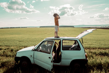 Boy standing on car roof in grassy field against cloudy sky