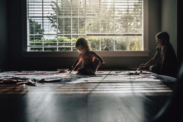 Sisters painting while sitting on floor against window at home