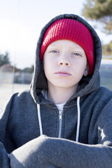 Portrait of confident boy wearing knit hat and hooded shirt