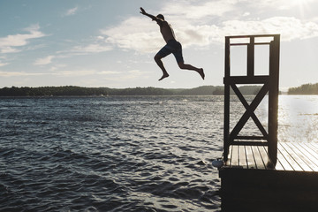 Carefree shirtless man jumping into Lake Rosseau against cloudy sky