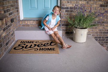Smiling girl with backpack sitting on doorstep by doormat