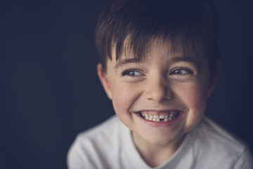 Close-up of cheerful boy clenching teeth while looking through sideways glance