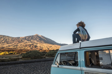 Carefree woman sitting on camper trailer against mountains and clear sky