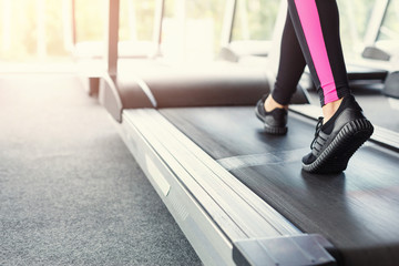 Woman's feet on treadmill in fitness club, healthy lifestyle