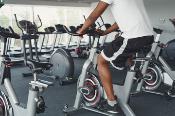 Man's legs on exercise bike in fitness club, healthy lifestyle