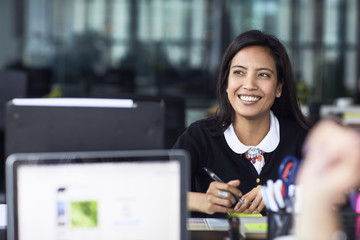 Smiling businesswoman looking away while working in office