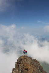High angle view of friends with arms around shoulders standing on Cheam Peak against sky amidst clouds