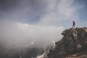 Side view of hiker standing on cliff against cloudy sky