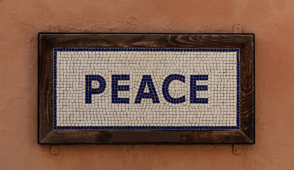 Word peace made from cubes. Mosaic pattern, wooden frame, warm brown background. Close up view.