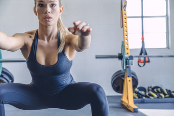Focused woman warming up with squats in gym