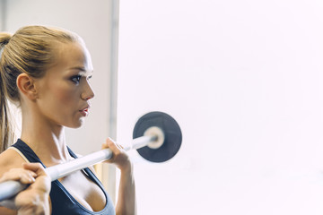 Side view of woman lifting barbell while exercising in brightly lit gym
