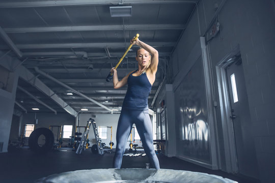 Woman hitting tire with sledgehammer while training at gym